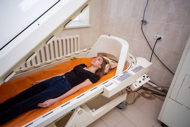 Una niña con una camiseta negra yace en una cámara hiperbárica, oxigenoterapia