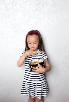 Una niña con una camiseta a rayas con rayas blancas y negras posando en una pared gris comiendo galletas de una caja grande