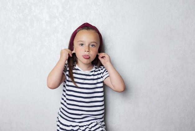 Una niña con una camiseta a rayas con rayas blancas y negras posando en la pared gris haciendo muecas