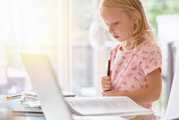 Niña en una camiseta rosa hace su tarea usando una computadora portátil. habitación luminosa con luz natural, chica independiente, educación.