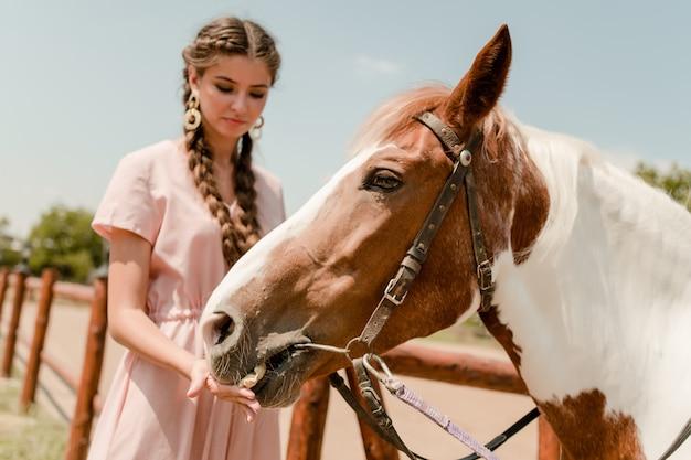 Niña de campo alimentando a un caballo en un rancho
