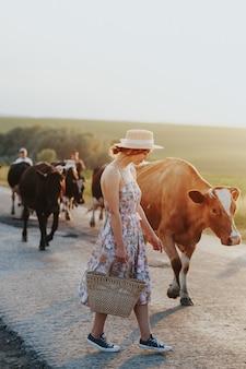 Niña en campo de granja con vacas en blanco y negro