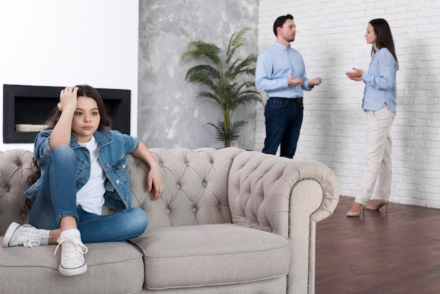 Niña cansada de padres discutiendo