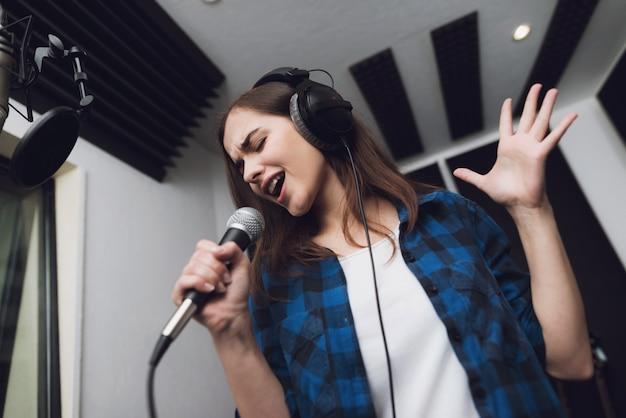 La niña canta su canción en un moderno estudio de grabación.