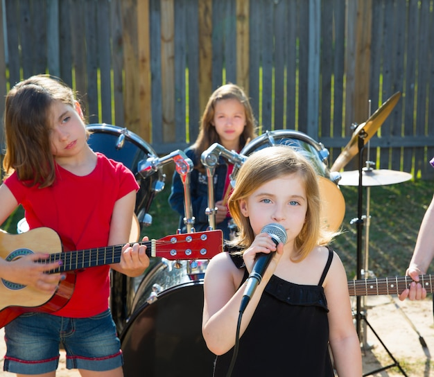 Niña cantante chica cantando tocando banda en vivo en el patio trasero