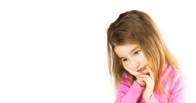 Niña con cara triste sostiene su mejilla con la mano - duele el diente. dolor de oído