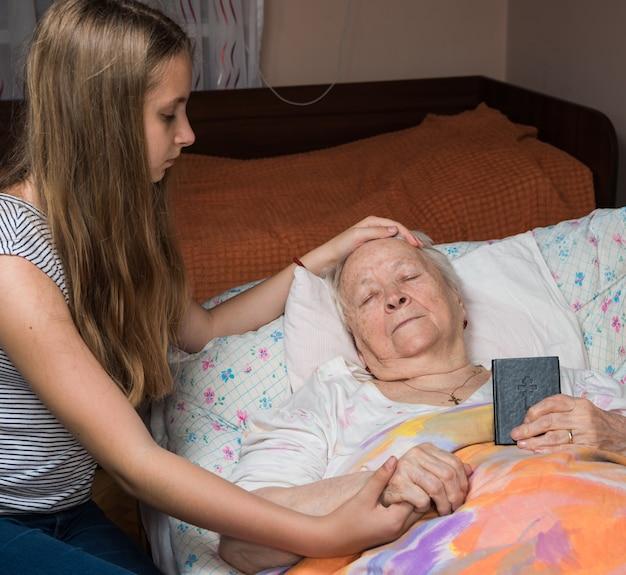 Niña cariñosa sosteniendo las manos de la anciana en la cama en casa