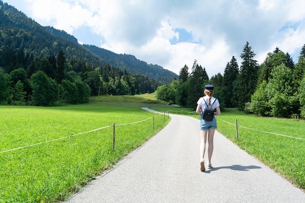 La niña va por la carretera en el fondo de las montañas.