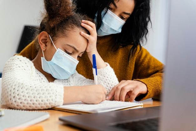 Niña en casa con máscara médica durante la escuela en línea con la hermana mayor