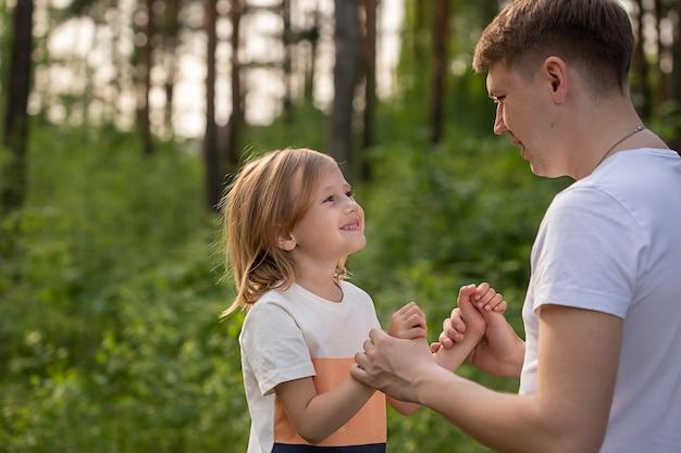 Niña caucásica de 6 años sosteniendo la mano de papá mirándose en el bosque. padre e hija jugando juntos, riendo y divirtiéndose. concepto de actividad familiar feliz