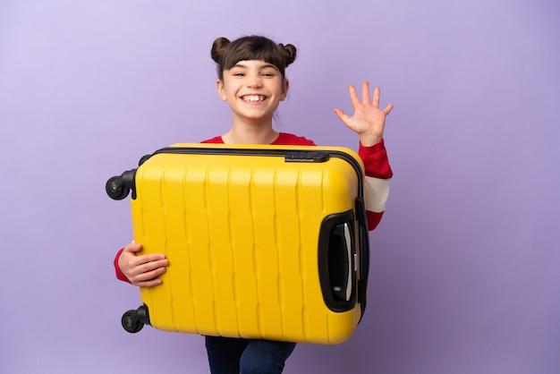 Niña caucásica aislada en la pared púrpura en vacaciones con maleta de viaje y saludando