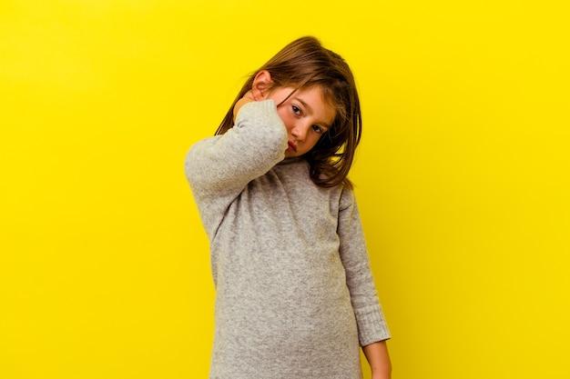 Niña caucásica aislada sobre fondo amarillo con dolor de cuello debido al estrés, masajeando y tocándolo con la mano.