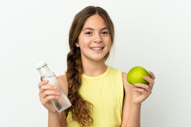 Niña caucásica aislada sobre fondo blanco con una manzana y con una botella de agua