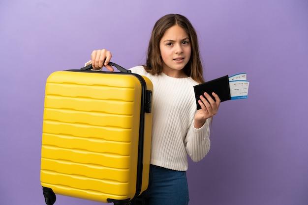 Niña caucásica aislada sobre fondo púrpura infeliz en vacaciones con maleta y pasaporte