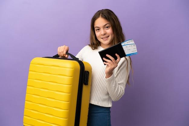 Niña caucásica aislada sobre fondo púrpura en vacaciones con maleta y pasaporte