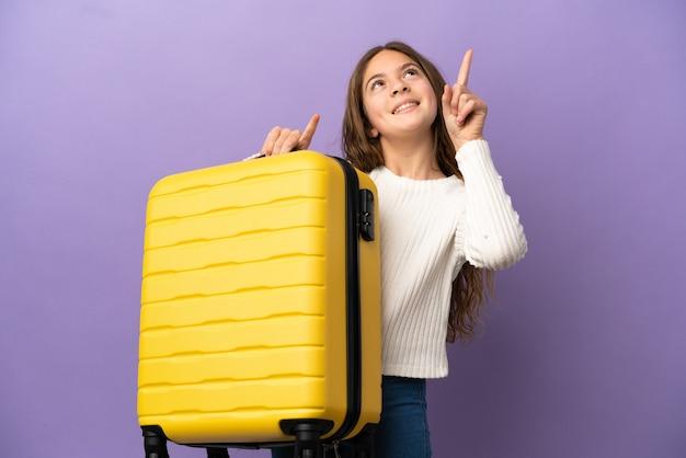 Niña caucásica aislada sobre fondo púrpura en vacaciones con maleta de viaje y apuntando hacia arriba