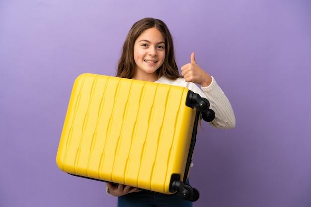 Niña caucásica aislada sobre fondo púrpura en vacaciones con maleta de viaje y con el pulgar hacia arriba
