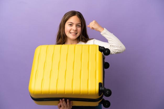 Niña caucásica aislada sobre fondo púrpura en vacaciones con maleta de viaje