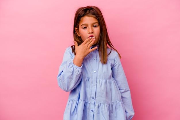 Niña caucásica aislada sobre fondo rosa bostezando mostrando un gesto cansado cubriendo la boca con la mano.