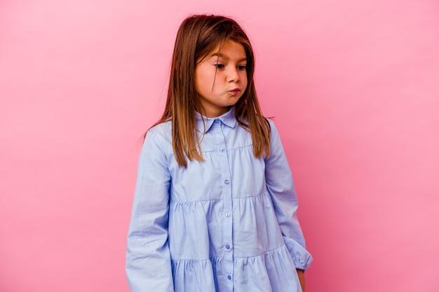 Niña caucásica aislada sobre fondo rosa confundida, se siente dudosa e insegura.