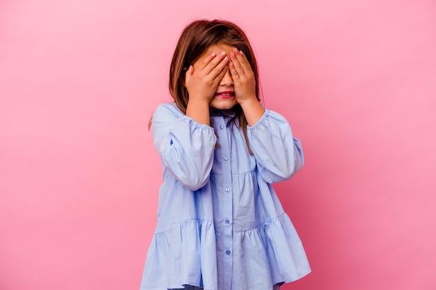 Niña caucásica aislada sobre fondo rosa cubre los ojos con las manos, sonríe ampliamente esperando una sorpresa.