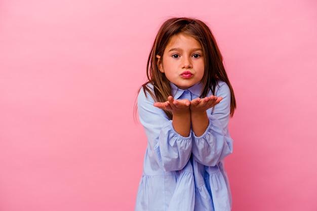 Niña caucásica aislada sobre fondo rosa doblando los labios y sosteniendo las palmas para enviar un beso al aire.