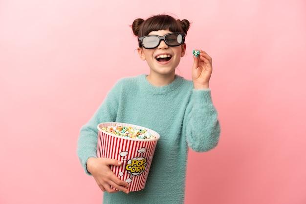 Niña caucásica aislada sobre fondo rosa con gafas 3d y sosteniendo un gran cubo de palomitas de maíz