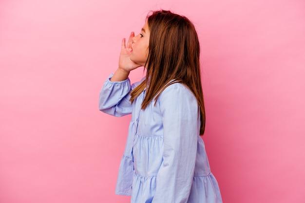 Niña caucásica aislada sobre fondo rosa gritando y sosteniendo la palma cerca de la boca abierta.