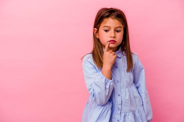 Niña caucásica aislada sobre fondo rosa mirando hacia los lados con expresión dudosa y escéptica.