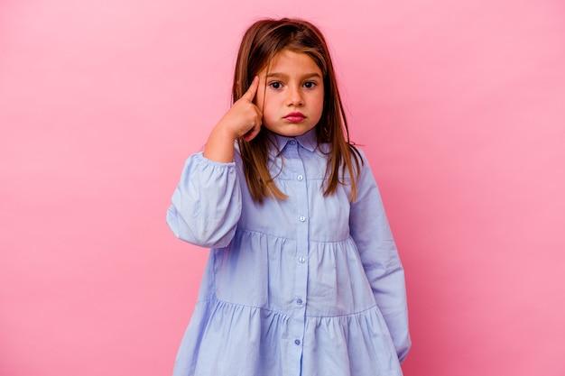 Niña caucásica aislada sobre fondo rosa señalando la sien con el dedo, pensando, centrado en una tarea.
