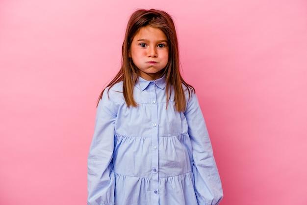 Niña caucásica aislada sobre fondo rosa sopla mejillas, tiene expresión cansada. concepto de expresión facial.