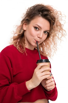 Niña caucásica con cabello rubio rizado bebe café y sonrisas, retrato aislado
