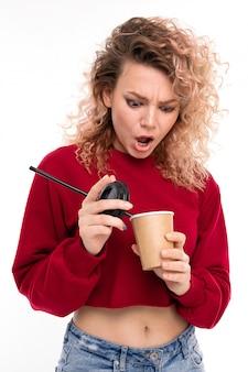 Niña caucásica con cabello rubio rizado bebe café y se sorprende, retrato aislado