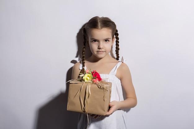 Niña caucásica con coletas y ojos oscuros de pie en un vestido sobre un fondo blanco tiene un regalo en las manos