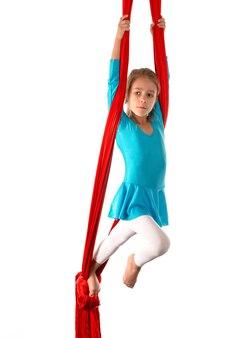 Niña caucásica concentrada en traje de baño azul hace ejercicios de gimnasia en una cinta aérea roja sobre un fondo blanco