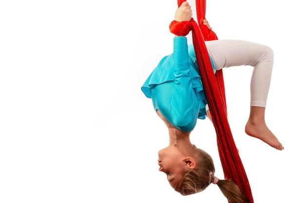 Niña caucásica concentrada en traje de baño azul hace ejercicios gimnásticos en una cinta aérea roja