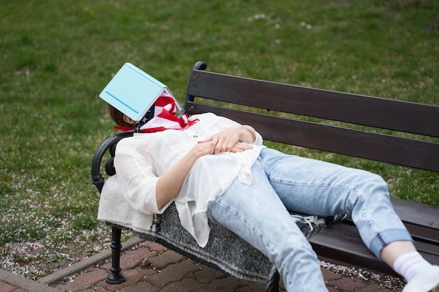 Niña caucásica durmiendo en el banco en el parque con la protección de la venda de la bandera americana en la cara durante el brote