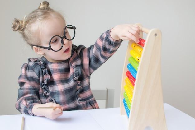 Niña caucásica con gafas redondas. pequeña maestra gafas divertidas humor. estilo retro