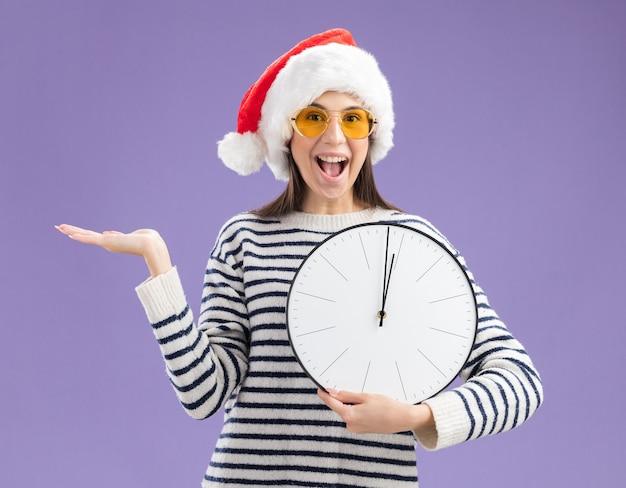 Niña caucásica joven sorprendida en gafas de sol con sombrero de santa sosteniendo el reloj y manteniendo la mano abierta