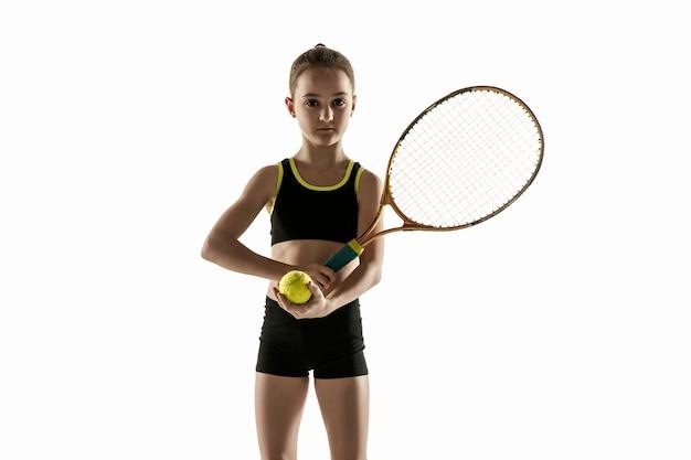 Niña caucásica jugando al tenis aislado sobre fondo blanco.