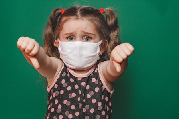 Niña caucásica con máscara médica y vestido de lunares que muestra el signo del pulgar sobre fondo verde durante la cuarentena y la pandemia de coronavirus 2020