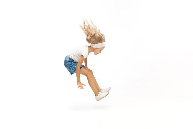 Niña caucásica pequeña y emocional saltando y corriendo aislado en blanco
