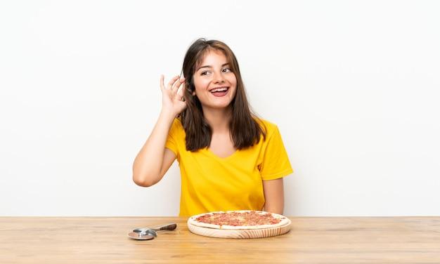 Niña caucásica con una pizza escuchando algo