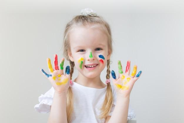 Niña caucásica que pinta con las manos coloridas pinta en casa educación temprana preparación para el desarrollo de la escuela preescolar juego de niños
