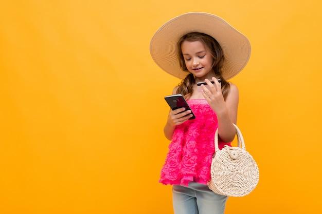 Niña caucásica en un sombrero de paja con una bolsa redonda tiene una tarjeta de crédito con una maqueta y un teléfono sobre un fondo amarillo