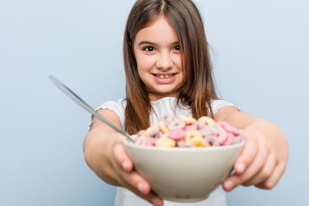Niña caucásica sosteniendo un tazón de cereal