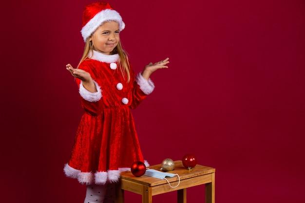 Niña caucásica con traje de santa y sombrero rojo confundida al elegir un accesorio de árbol de navidad, no entiende el significado de la máscara. pared aislada roja.