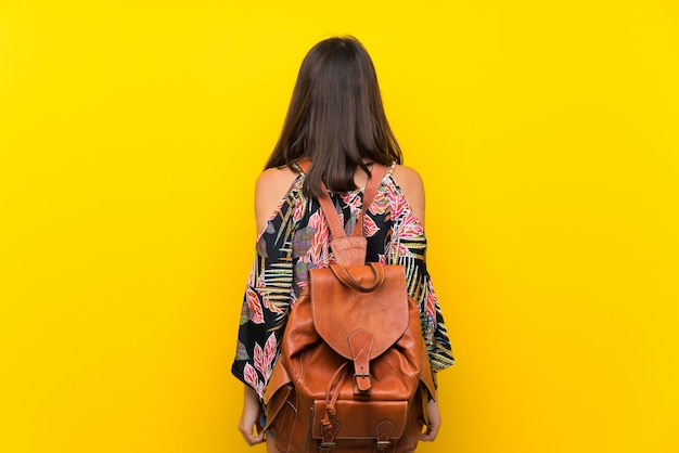Niña caucásica en vestido colorido sobre pared amarilla aislada con mochila