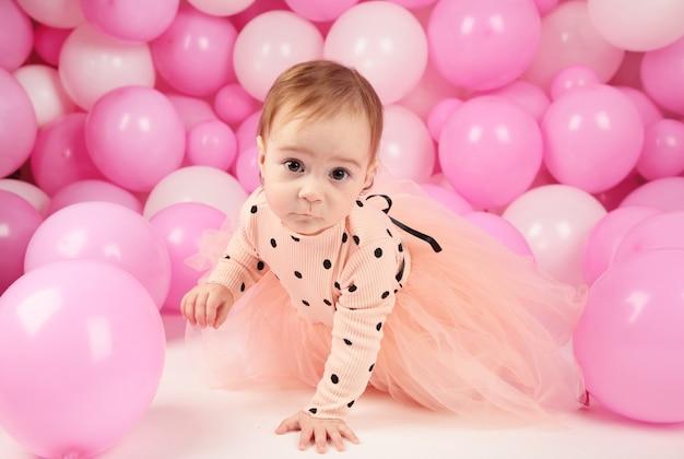 La niña celebra su primer cumpleaños. chica sobre fondo de globos rosas. vista superior