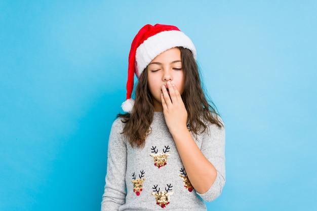 Niña celebrando el día de navidad bostezando mostrando un gesto cansado que cubre la boca con la mano.